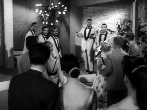 B/W 1956 The Moonglows performing 'Over + Over Again' on stage in front of small audience / feature