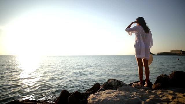 der schönste ort der welt. frau in der nähe des ozeans. sonnenuntergangszeit. sonne-kleid und hut - sexy teen stock-videos und b-roll-filmmaterial