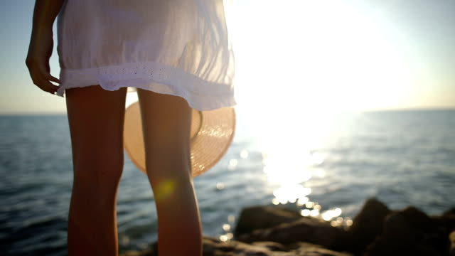 The most beautiful place in the world.Woman near the ocean. Sunset time. Sun dress and hat