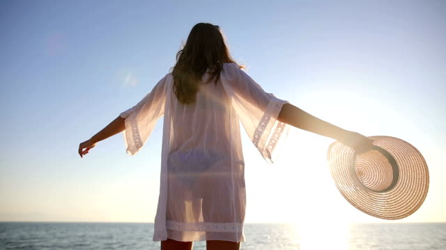 the most beautiful place in the world.woman near the ocean. sunset time. sun dress and hat - steps stock videos & royalty-free footage
