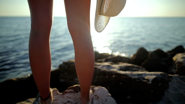 der schönste ort der welt. frau in der nähe des ozeans. sonnenuntergangszeit. sonne-kleid und hut - griechenland stock-videos und b-roll-filmmaterial