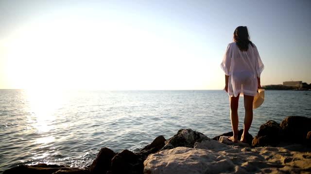 Der schönste Ort der Welt. Frau in der Nähe des Ozeans. Sonnenuntergangszeit. Sonne-Kleid und Hut
