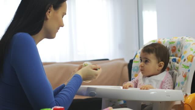 vídeos de stock, filmes e b-roll de a matriz que alimenta seu bebê com um papa de aveia da fruta sem alarido - comida de bebê