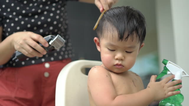 the mother gives her son's haircut at home during coronavirus quarantine. - hairstyle stock videos & royalty-free footage