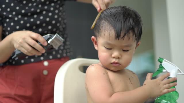vídeos de stock e filmes b-roll de the mother gives her son's haircut at home during coronavirus quarantine. - estilo de cabelo