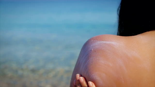 the mother puts the daughter on the body a protective sunscreen - sunbathing stock videos and b-roll footage
