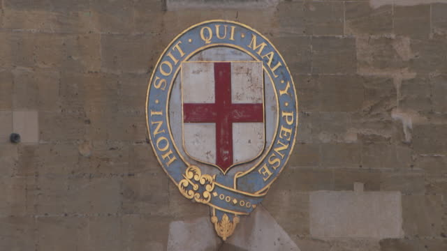The motto of the Order of the Garter 'HONI SOIT QUI MAL Y PENSE' encircles a painted St George's Cross on a wall at Windsor Castle UK FKAU104L Clip...