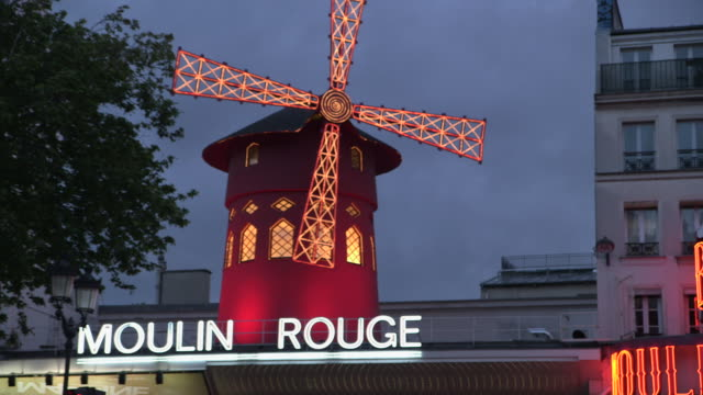 the moulin rouge's red windmill turns at dusk, pigalle, paris, france. - cabaret stock videos & royalty-free footage