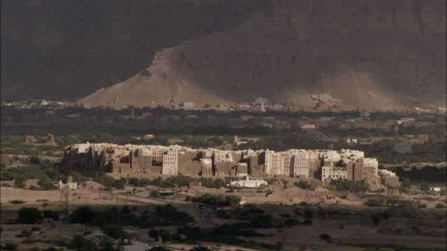 The mud-brick city of Shibam lies in a low desert valley in Yemen.