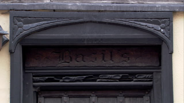 the name basil's is carved over a medieval cottage door. available in hd. - lavenham stock-videos und b-roll-filmmaterial