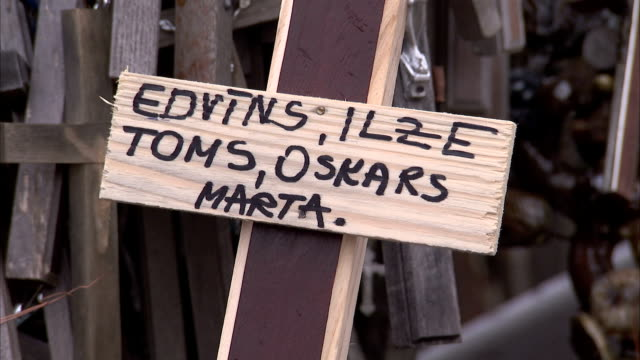 The names of departed loved ones cover a wooden cross. Available in HD.