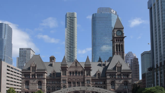 vídeos de stock e filmes b-roll de the nathan phillips square and the urban skyline. the image contrasts the romanesque revival old city hall with the modern designed skyscrapers of... - alto contraste