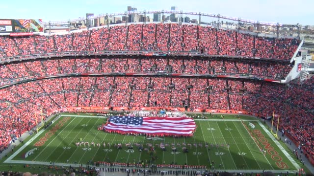 THe National Anthem performed before Denver Broncos game at Sports Authority Field at Mile High A giant flag is unfurled in the stadium for the...