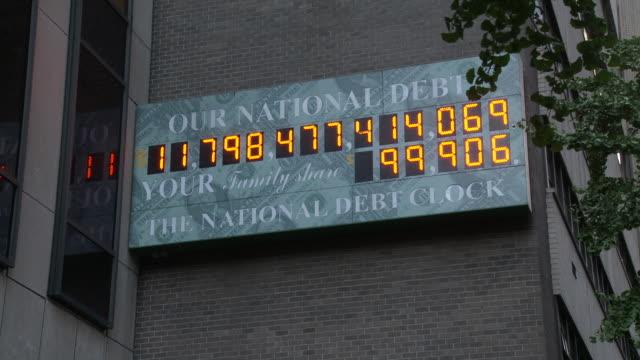 the national debt clock ticks away in a display sign in manhattan. - statsskuldklockan bildbanksvideor och videomaterial från bakom kulisserna