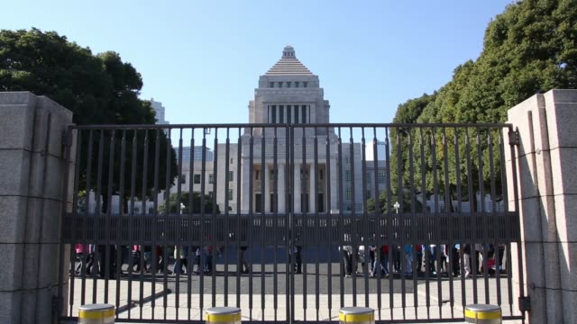 The National Diet building is seen through a gate in Tokyo Japan on Monday Dec 8 Tour groups walk past a gate outside the National Diet building...