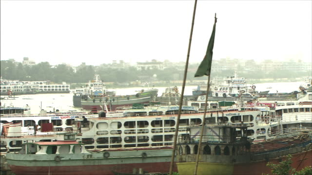 the national flag of bangladesh and a lot of boats at anchor. - flag of bangladesh stock videos & royalty-free footage