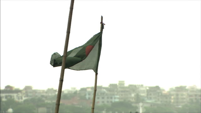 the national flag of bangladesh: pan left; boatslip: long shot. - flag of bangladesh stock videos & royalty-free footage