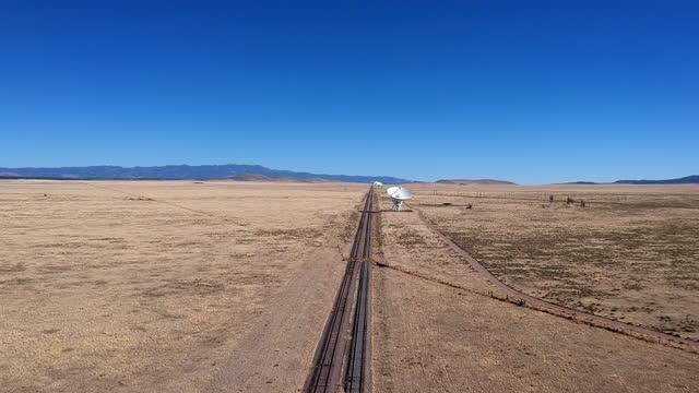 vídeos y material grabado en eventos de stock de el observatorio nacional de radioastronomía o el very large array en socorro, nuevo méxico, con las grandes vías del tren de posicionamiento desplegándose hacia un enorme satélite en la distancia. - espacio y astronomía