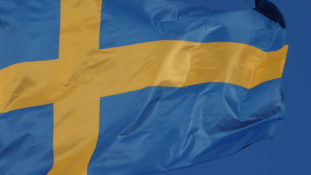 the national swedish flag waving in the wind. - swedish flag stock videos and b-roll footage