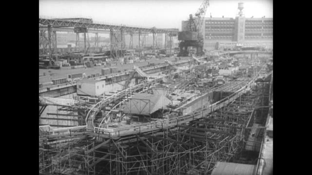 the naval ship yard in brooklyn / shipyard looks clean and empty / footage cuts to vintage clip of ship being launched in front of crowd in 1920s... - shipyard stock videos & royalty-free footage