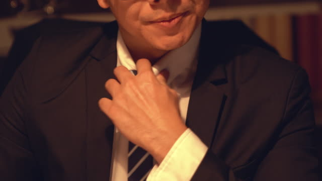 the nervous man straightens collar on the shirt. asian young businessman adjusting his tie with a serious thoughtful expression, looking away. - bribing stock videos & royalty-free footage