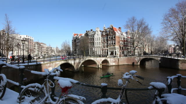 The Netherlands, Amsterdam, Canal houses in canal called Keizersgracht. Bicycles. Winter, snow