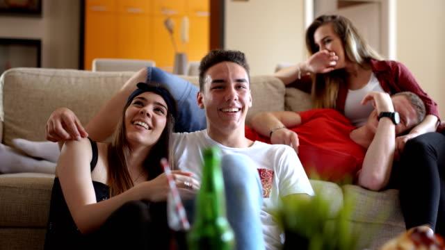 vídeos de stock, filmes e b-roll de o novo casal está ficando vermelho, enquanto seu amigo está provocando-lhes - assistir tv