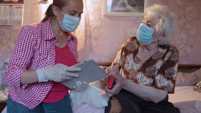 the new normal. charge sharing. young adult wearing protective face mask visiting a senior woman at her home, supplying her with external power bank for wireless devices to keep her connected with the world. illness prevention during covid-19 pandemic. - community care stock videos & royalty-free footage
