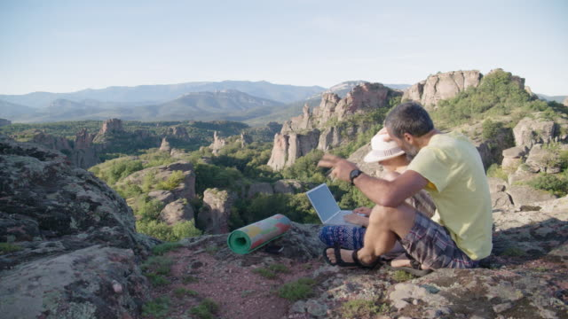 the new normal. couple travelers sitting near a beautiful landscape in nature and talking online to a friend remotely while covid-19 pandemic. flatten the curve by social distancing. - red rocks stock videos & royalty-free footage