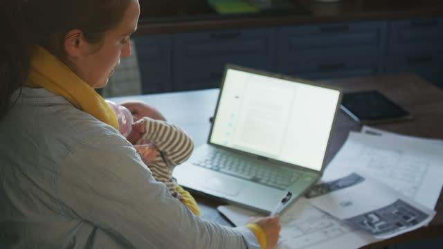 die neue normalität. neue home-office-einrichtung. frau mit einem kleinen kind, die zu hause während covid-19 pandemie arbeitet. glätten sie die kurve, indem sie online arbeiten und sich um ein neugeborenes baby kümmern. - single mother stock-videos und b-roll-filmmaterial