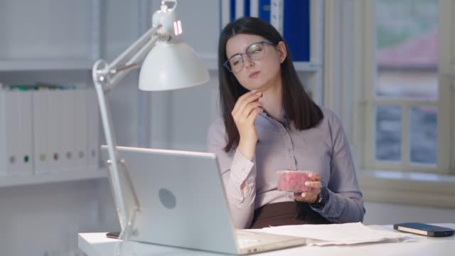 vídeos y material grabado en eventos de stock de la nueva normal. nueva configuración de oficina. mujer trabajando sola en el nuevo espacio de oficinas mientras covid-19 pandemia. tomar un descanso con un aperitivo de frambuesa. - hacer un descanso