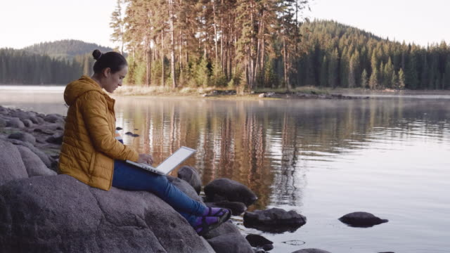 the new normal. new office setups. woman solo traveler sitting near a mountain lake and working on her laptop while covid-19 pandemic.vacations and leisure time. flatten the curve by social distancing. - natural parkland stock videos & royalty-free footage
