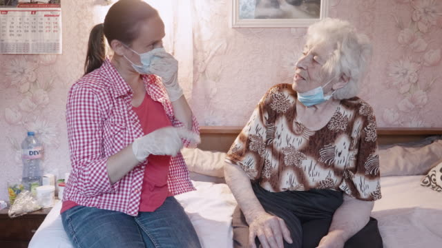 the new normal. young adult with a protective face mask visiting a senior woman at her home, keep her connected with the world. illness prevention during covid-19 pandemic. - 80 89 years stock videos & royalty-free footage