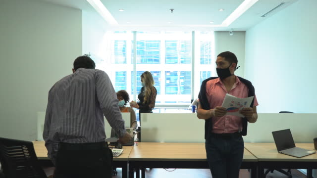 the new normally in the office.two latino workers greet each other inside the office.this happens during covid 19 - colombian ethnicity stock videos & royalty-free footage
