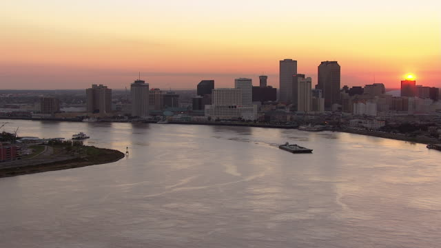 the new orleans skyline looms over the mississippi river. - river mississippi stock videos & royalty-free footage