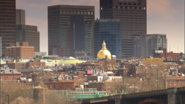 The new State House w/ gold dome on top of Beacon Hill w/ city highrises BG partial Longfellow Bridge FG