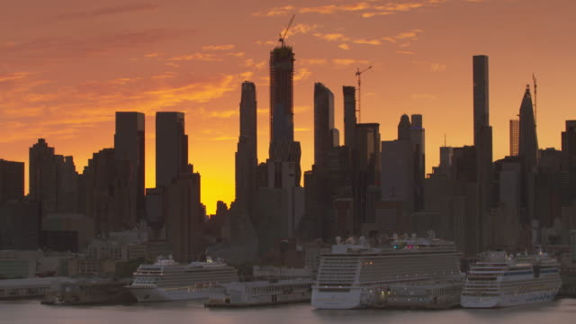 the new york city skyline at dawn. cruise ships line the harbor. - cruising stock videos & royalty-free footage