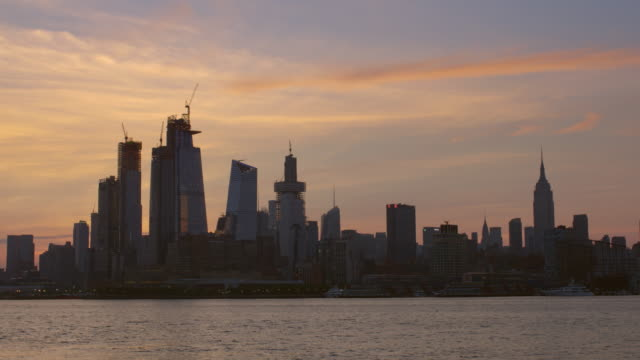 the new york city skyline at sunrise  the hudson yards have the sun rising behind. - 逆光点の映像素材/bロール