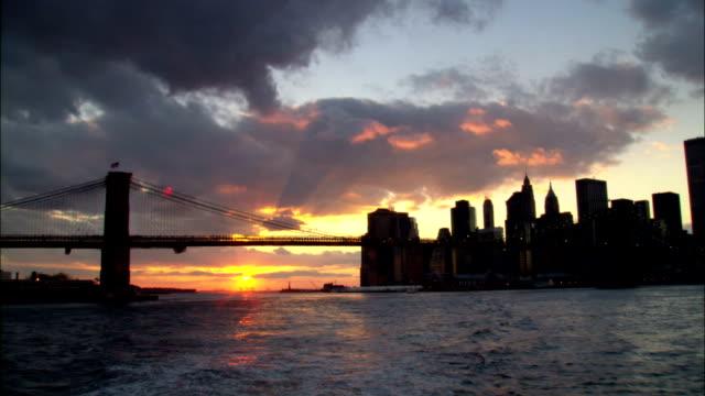 vídeos de stock e filmes b-roll de the new york city skyline stands in silhouette under an afternoon sky near the manhattan and brooklyn bridges. - ponte de manhattan