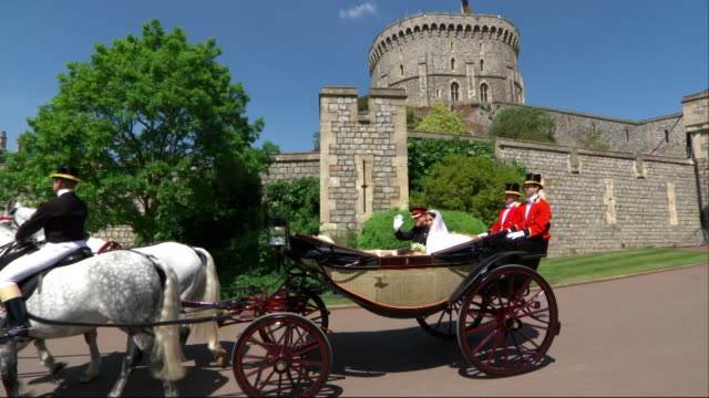 The newlywed Duke and Duchess of Sussex travel by horsedrawn carriage through a part of the grounds of Windsor Castle