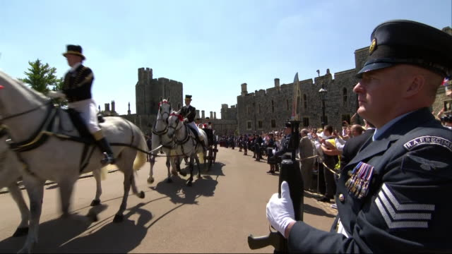 The newlywed Duke and Duchess of Sussex wave as they travel by horsedrawn carriage through the grounds of Windsor Castle