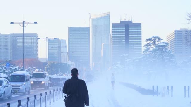 the next morning of winter snowstorm at chiyoda-ku tokyo japan – january. 23 2018. hibiya district high-rise buildings stand beyond the snowy uchibori-dori during the mist in the morning. - 雪点の映像素材/bロール