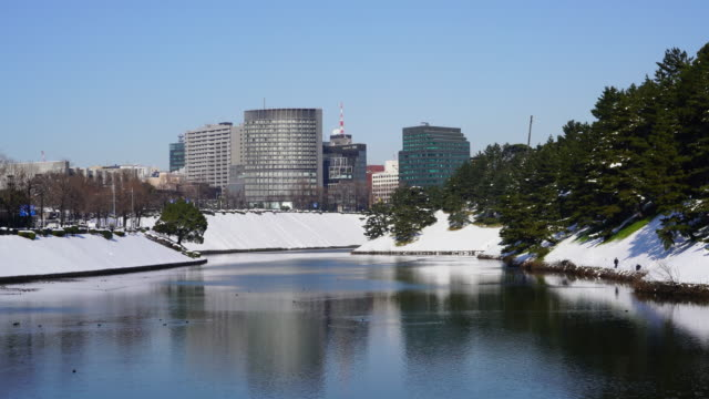 The next morning of winter snowstorm at Chiyoda-ku Tokyo Japan – January. 23 2018. High-rise buildings stand behind snowy Imperial Palace Moat, which are reflecting to the water surface of the moat.