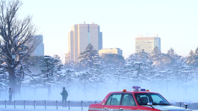 The next morning of winter snowstorm at Chiyoda-ku Tokyo Japan – January. 23 2018. Kasumigaseki district high-rise buildings stand over the snowy Imperial Palace Forest from Kokyogaien National Park along the Uchibori-dori during the mist in the morning.