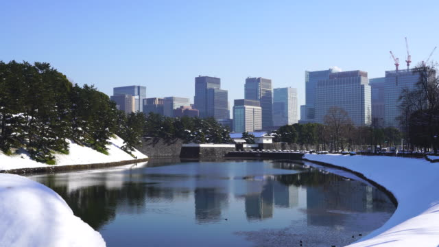 The next morning of winter snowstorm at Chiyoda-ku Tokyo Japan – January. 23 2018. Marunouchi district and Hibiya district high-rise buildings stand behind the snowy Imperial Palace Moat, which are reflecting to the water surface of the moat.