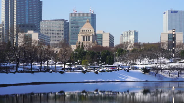 the next morning of winter snowstorm at chiyoda-ku tokyo japan – january. 23 2018. the national diet of japan building and nagatacho district buildings stand behind the snowy imperial palace moat. - organised group stock videos & royalty-free footage