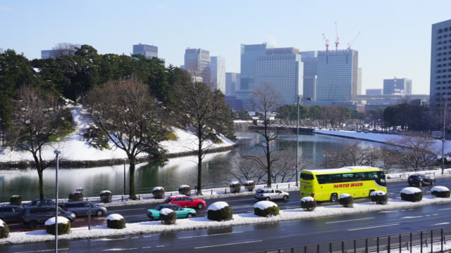 The next morning of winter snowstorm at Chiyoda-ku Tokyo Japan – January. 23 2018. Cars run on Uchibori Dori along the snowy Imperial Palace Moat. Hibiya district high-rise buildings stand over the Imperial Palace Moat.