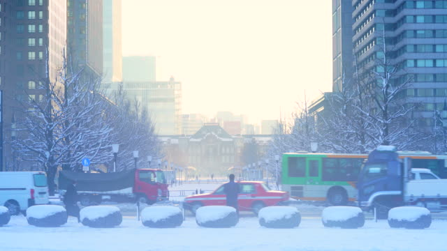 The next morning of winter snowstorm at Marunouchi Chiyoda-ku Tokyo Japan – January. 23 2018. The morning sun illuminates the snowy cityscape, which are sky, lines of ginkgo trees, street and skyscrapers around the Tokyo Station.