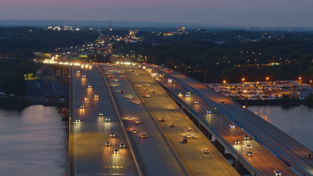 vidéos et rushes de la vue aérienne de nuit sur le pont du gouverneur alfred e. driscoll sur la rivière raritan, new jersey, reliait les villes de keasbey et melrose. des images vidéo prises par drone avec la caméra statique. - new jersey