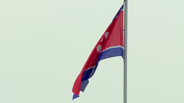 the north korean flag flies from a flagpole in pyongyang - pyongyang stock videos and b-roll footage